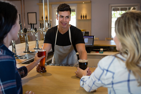 bartending: Bartender serving drinks to young female friends at bar counter
