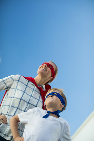 Smiling mother and son pretending to be superhero in garden Stock Photo