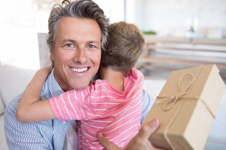 Father embracing son while receiving gift in living room at home
