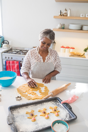 Smiling senior woman preparing cookies in kitchen at home
