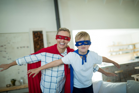 pretending: Mother and son pretending to be superhero in living room at home