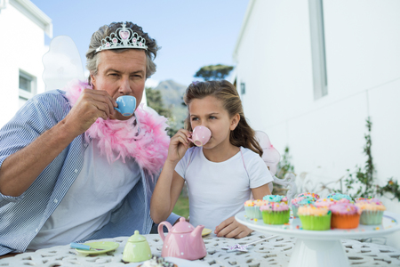 pretending: Father and daughter in fairy costume having a tea party at garden