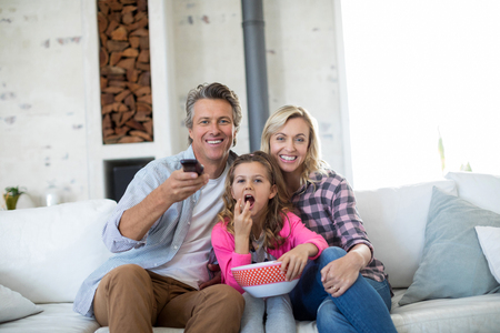 changing channel: Smiling family watching television while having popcorn in living room at home