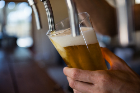 frothy: Cropped hand of bartender pouring beer from tap in glass at restaurant