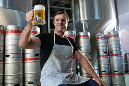 Portrait of smiling worker holding beer glass at warehouse Stock Photo