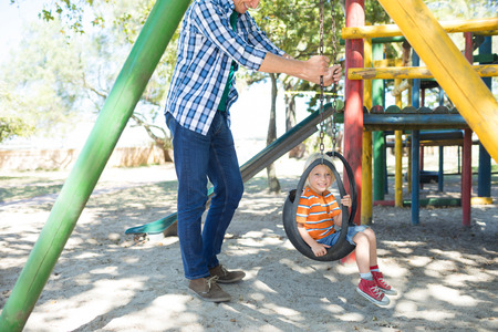 low section: Low section of father pushing son sitting on swing at playground Stock Photo