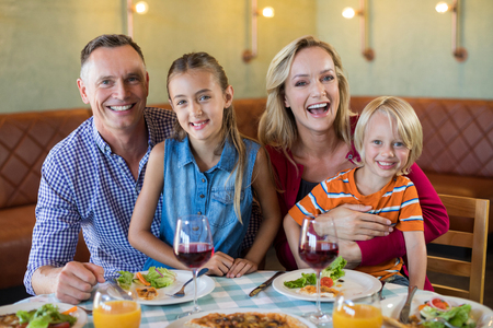 Portrait of cheerful family sitting at restaurant Stockfoto