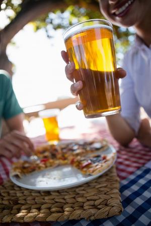 Bebouwd beeld van het bierglas van de vrouwenholding bij lijst in openluchtrestaurant