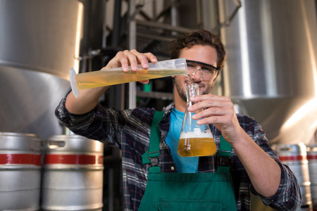 destilacion: Retrato de trabajador sonriente vertiendo cerveza en vaso en fábrica