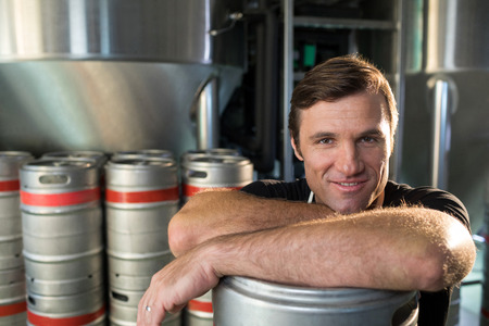 Close up portrait of smiling worker leaning on kegs at warehouse Stock Photo