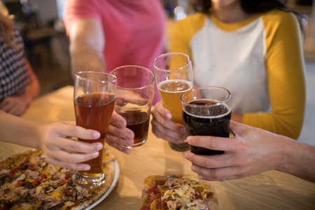 Cropped hands of friends toasting drinks at table in restaurant