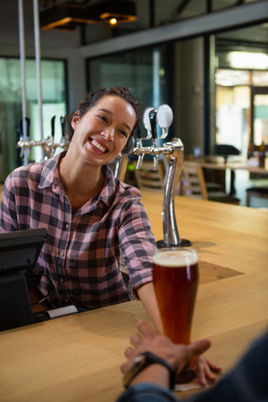 frothy: Happy barmaid serving drink to male customer at bar counter Stock Photo