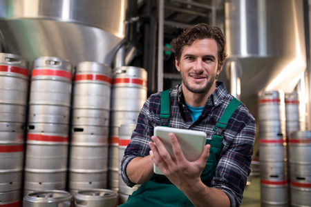 Portrait of worker using tablet computer while sitting in warehouse Stock Photo