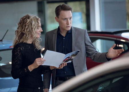 Female customer showing brochure to salesman in car showroom