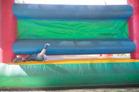 low section: Low section of boy playing on bouncy castle at playground Stock Photo