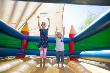 Portrait of happy siblings with arms raised jumping on bouncy castle at playground