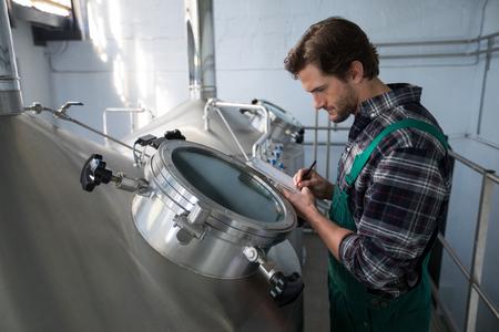 Worker examining storage tanks at warehouse
