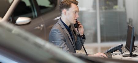 les ventes parlent au téléphone tout en utilisant l & # 39 ; ordinateur dans le bureau à l & # 39 ; automobile Banque d'images