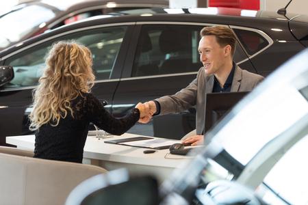 車のショールームで座っているデスクながら女性客とのハンドシェイクを行うセールスマンを笑顔