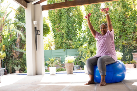 Woman with arms raised holding dumbbells while sitting on fitness ball Reklamní fotografie
