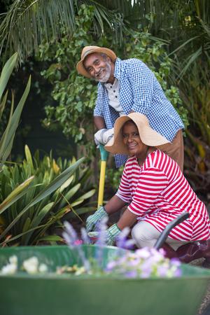 Portrait of happy senior couple gardening in yard Stock Photo