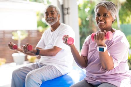 Portrait of senior couple lifting dumbbells exercising in yar