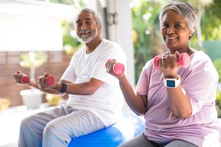 Portrait of senior couple lifting dumbbells exercising in yar