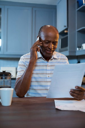 Smiling man reading document while using phone in kitchen at home Stock Photo