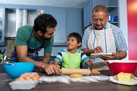 generation gap: Man using table while standing by father and son preparing food in kitchen at home
