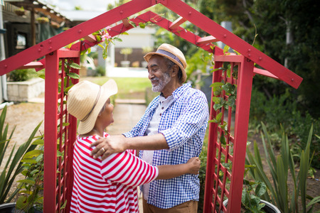 Smiling senior couple standing face to face by metallic structure in yard