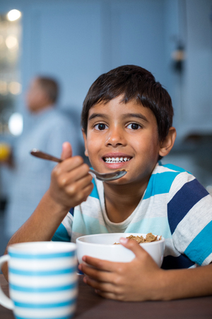 generation gap: Close up portrait of boy having cereal breakfast at home Stock Photo