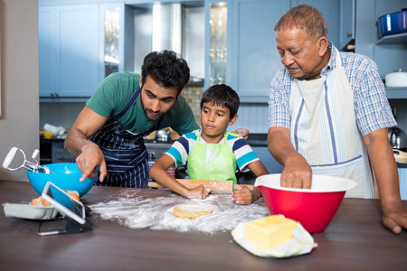 generation gap: Man showing tablet to son while preparing food with grandfather in kitchen at home Stock Photo