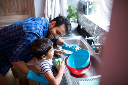 High angle view of father and son cleaning utensils at home
