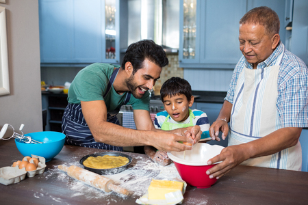 generation gap: Boy looking at father breaking egg while preparing food with grandfather in kitchen at home Stock Photo
