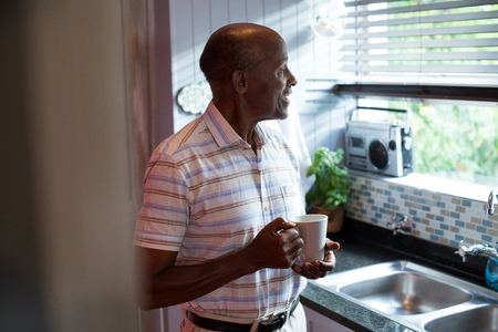 one parent: Thoughtful man with coffee standing by window at home Stock Photo