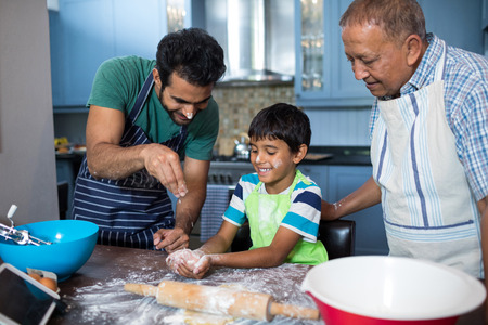 Father sprinkling flour on sons hand while preparing food with grandfather in kitchen at home Stock Photo