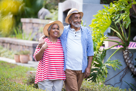 Smiling senior couple with arm around walking in yard