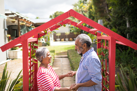 High angle view of couple holding hand while standing by metallic structure in yard Stock Photo