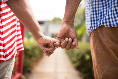 Cropped image of senior couple holding little fingers while standing in yard