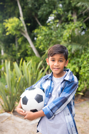 Portrait of smiling boy holding soccer ball while standing at park Stock Photo