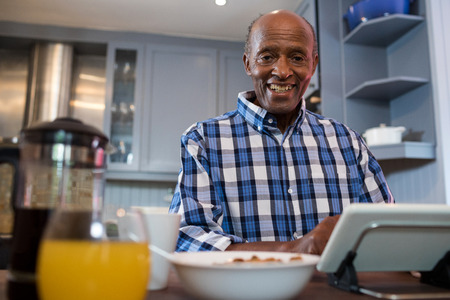 Portrait of senior man using tablet while sitting at table in kitchen Stock Photo