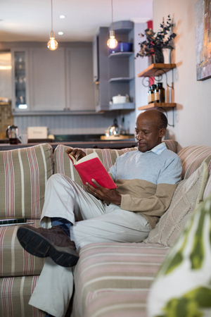 Senior man reading book while sitting on sofa in living room at home