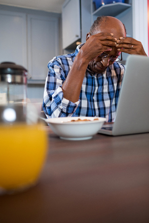 receding: Worried man using laptop while sitting at home