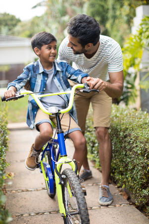 Father talking to son while cycling in yard