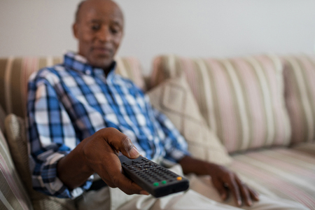 receding: Man holding remote control while sitting on sofa in living room at home Stock Photo