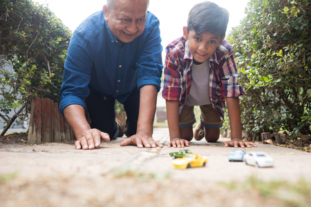 Boy and grandfather playing with toy cars while kneeling on pavement in yard Standard-Bild