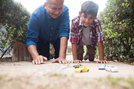 aplaudiendo: Muchacho y abuelo que juegan con los coches del juguete mientras que arrodillan en pavimento en yarda