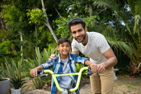 Portrait of father with son sitting on bicycle in yard Stock Photo