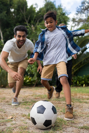 generation gap: Playful family playing soccer on field in yard
