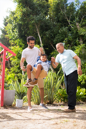generation gap: Playful father and grandfather with boy at park during sunny day